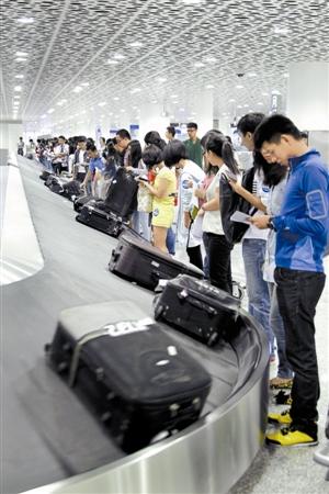 国际航班行李提取厅,乘客正在领取行李.深圳特区报记者 陈富 摄